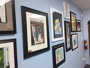 Art displayed on the wall at Stop N Mail Melbourne, Fl. Shows a series of watercolor paintings.