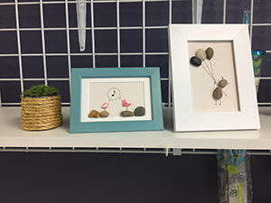 Photograph of two pieces of pebble art on display at Stop N Mail Melbourne, Fl.