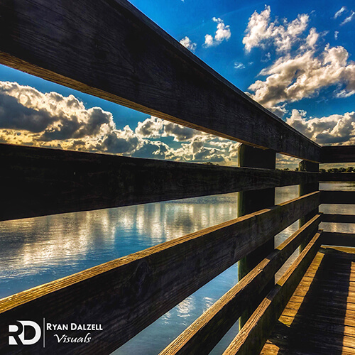 Image of the water and clouds through the slats in a dock railing. Image taken by Ryan Dalzell of Ryan Dalzell Visuals.