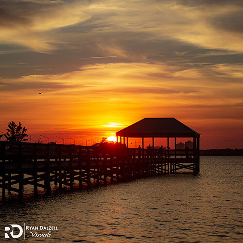 Image of a Florida Sunset across the water with a dock and people enjoying the view. Image taken by Ryan Dalzell of Ryan Dalzell Visuals.